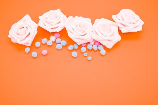 Nahaufnahmeaufnahme der rosa rosen und der bunten pompons lokalisiert auf orange hintergrund