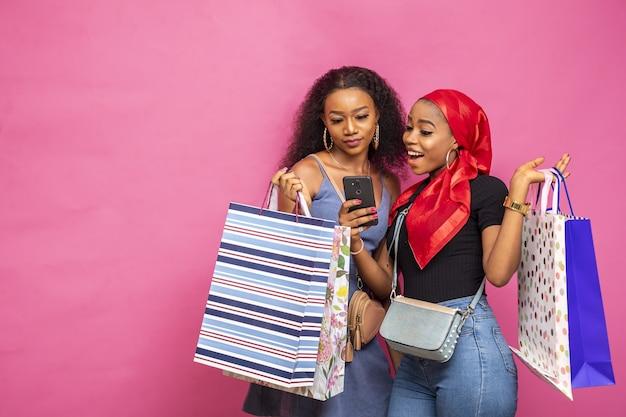 Nahaufnahmeaufnahme der schönen jungen afrikanischen frauen mit einkaufstaschen