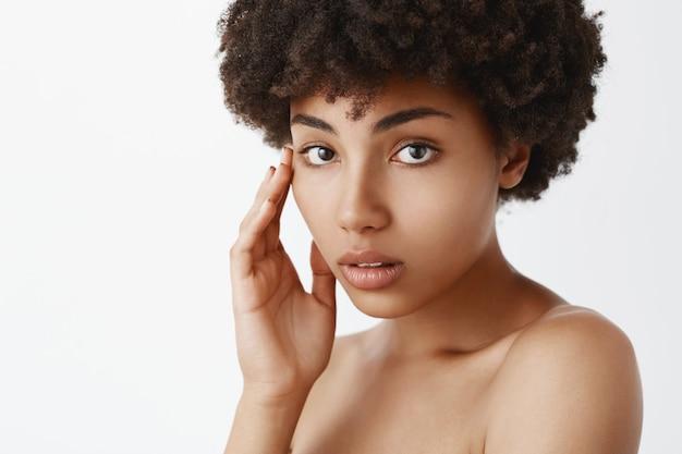 Nahaufnahmeaufnahme der sinnlichen und zarten schönen afroamerikanerfrau mit reiner haut, die gesicht sanft berührt und mit niedlichen und liebevollen emotionen nackt posiert