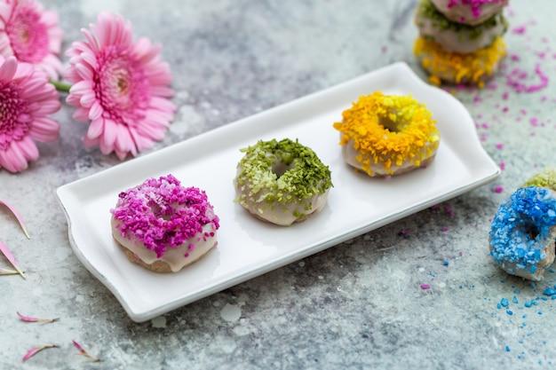 Nahaufnahmeaufnahme der tischplatte der veganen rohen bunten donuts