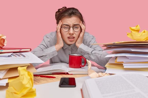 Nahaufnahmeaufnahme der unzufriedenen frau hält hände an schläfen, runzelt die stirn, hat müdigkeit ausdruck, trägt runde brille
