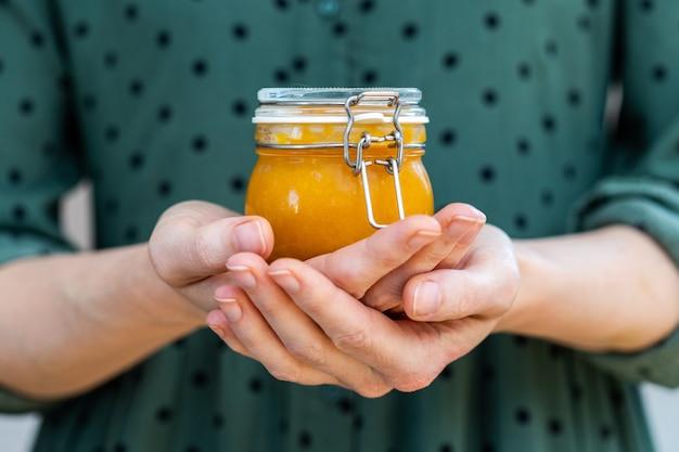 Nahaufnahmeaufnahme der weiblichen hände, die eine hausgemachte vegane rohe aprikosenmarmelade in einem glas halten