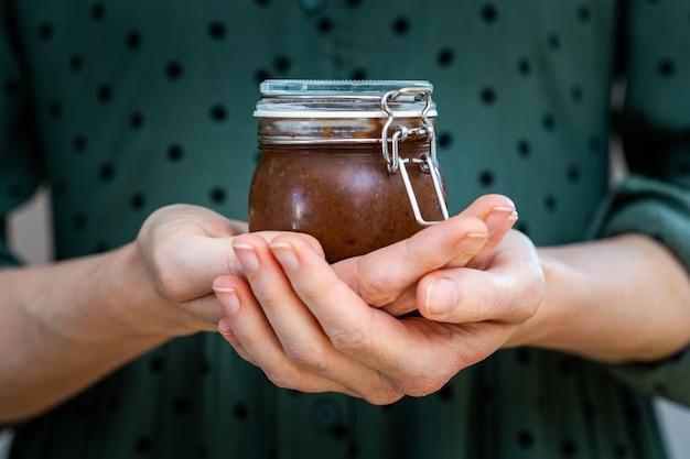 Nahaufnahmeaufnahme der weiblichen hände, die eine hausgemachte vegane rohe pflaumenmarmelade in einem glas halten