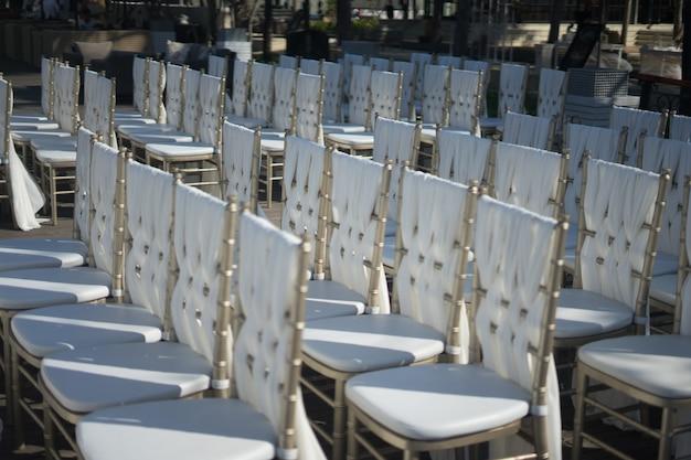 Nahaufnahmeaufnahme der weißen stühle für die gäste einer hochzeitszeremonie