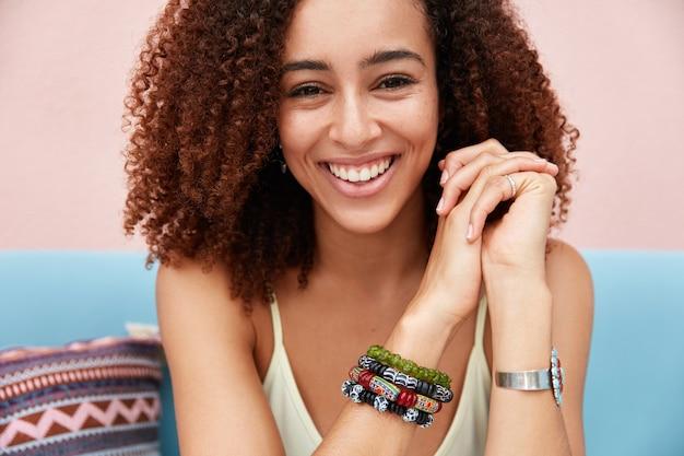Nahaufnahmeaufnahme der zufriedenen reizenden fröhlichen afrikanischen frau mit lockigem dunklem haar, trägt stilvolles armband, glücklich verbringen freizeit mit freund in gemütlichem café