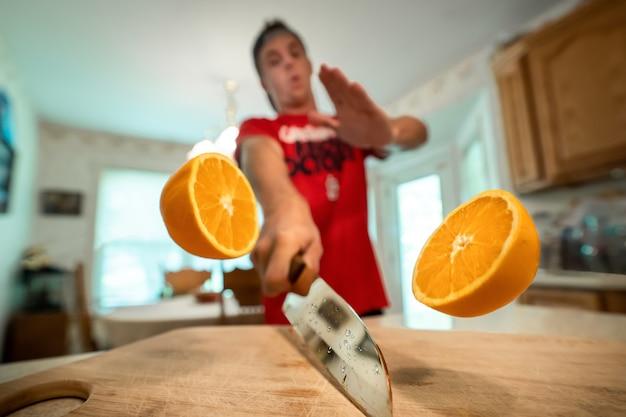 Nahaufnahmeaufnahme der zwei hälften einer orange in der luft, die von einem mann im hintergrund geschnitten wird