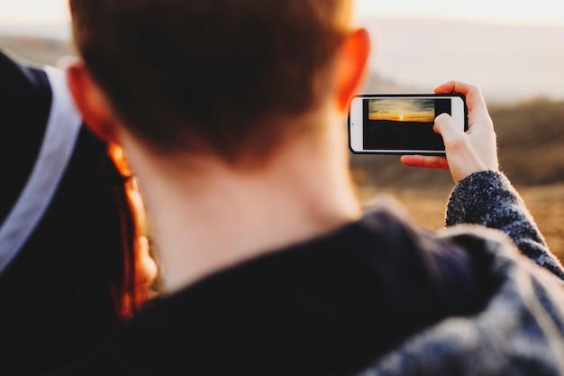 Nahaufnahmeaufnahme des anonymen paares, das smartphone verwendet, um foto des erstaunlichen sonnenuntergangs in der landschaft zu machen