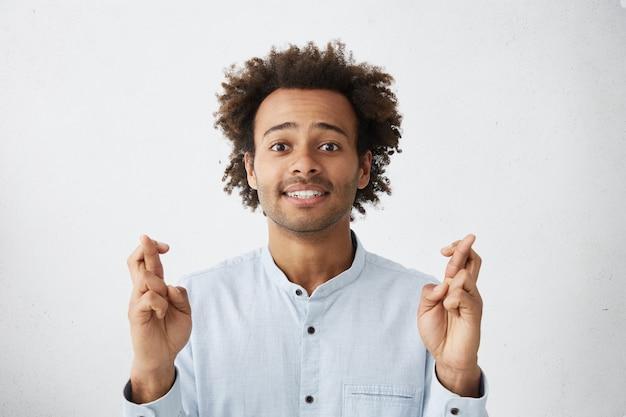 Nahaufnahmeaufnahme des attraktiven jungen angestellten, der hofft, bei der arbeit befördert zu werden