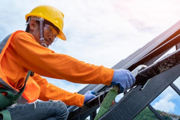 Nahaufnahmeaufnahme des bauarbeiters, der sicherheitsgurt trägt und in der höhe oben auf dem neuen dach arbeitet.
