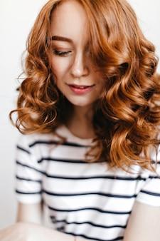 Nahaufnahmeaufnahme des bezaubernden weiblichen modells mit glänzendem gewelltem haar. innenfoto des modischen kaukasischen mädchens, das mit geschlossenen augen aufwirft.