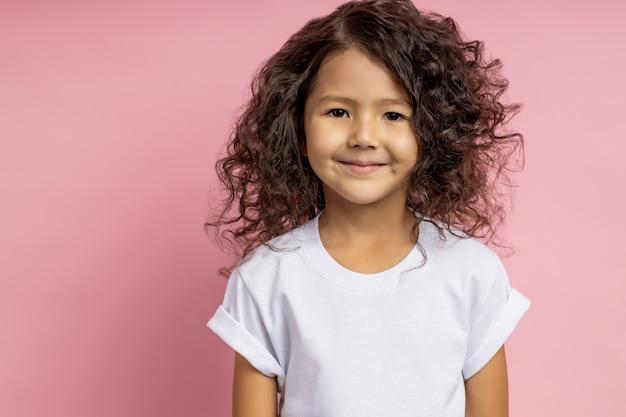 Nahaufnahmeaufnahme des charmanten kaukasischen kleinen mädchens im weißen t-shirt, mit freundlichem, freundlichem blick, der mit niedlichem lächeln schaut und gegen rosa wand aufwirft. glückliche kindheit, kindliche unschuld, kinderkonzept