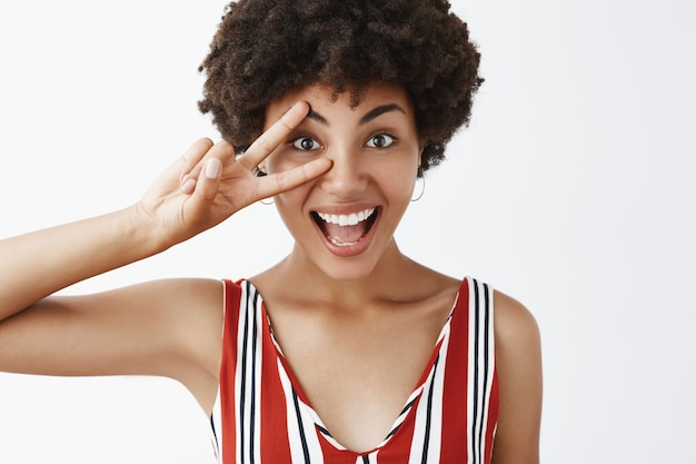 Nahaufnahmeaufnahme des freudigen optimistischen und glücklichen disco-mädchens mit afro-frisur in gestreifter bluse, die sieg oder friedenszeichen über auge zeigt und breit lächelnd glücklich und amüsiert fühlt