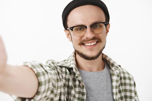 Nahaufnahmeaufnahme des freundlichen gutaussehenden ordentlichen kerls in der schwarzen trendigen mütze und in den gläsern mit dem schnurrbart, der breit lächelt, während er selfie nimmt