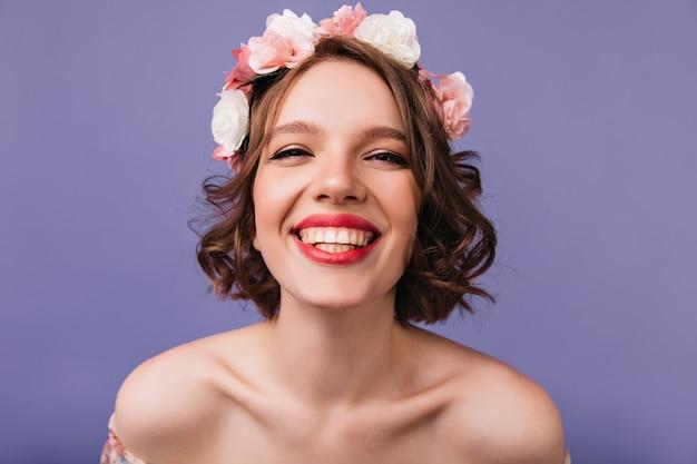 Nahaufnahmeaufnahme des fröhlichen weißen mädchens mit rosa blumen im haar. emotionale kaukasische dame lächelnd.