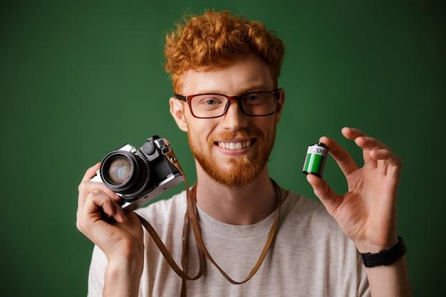 Nahaufnahmeaufnahme des jungen bärtigen hipsters des lesekopfes, der retro-fotokamera und kamerarolle hält