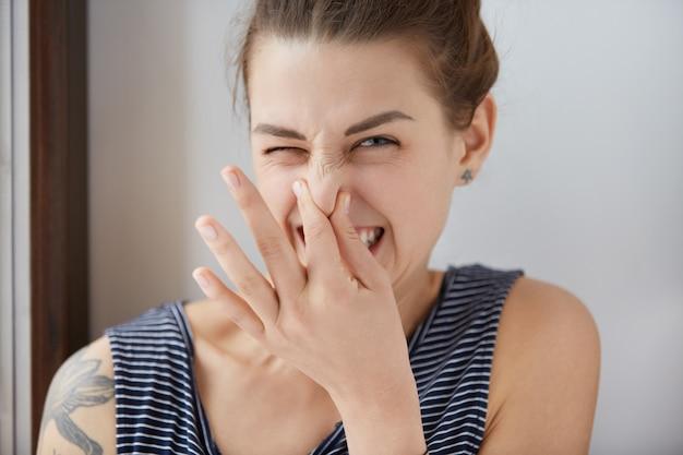 Nahaufnahmeaufnahme des kaukasischen mädchens, das ekel zeigt und ihre nase kneift, um schlechten geruch zu vermeiden. brünettes mädchen mit haarsträhnen, die augen in abneigung gegen schrecklichen gestank verengen. negative emotionen, böse gefühle.