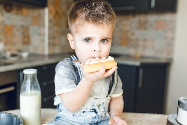 Nahaufnahmeaufnahme des lustigen kindes, das auf dem küchentisch sitzt und einen kuchen isst. er ist mit mehl bedeckt und sieht lustig aus.