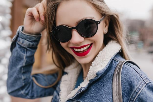 Nahaufnahmeaufnahme des romantischen kaukasischen mädchens, das mit schönem lächeln aufwirft. außenporträt der dame mit dunklem haar, das im frühlingswochenende durch stadt geht.
