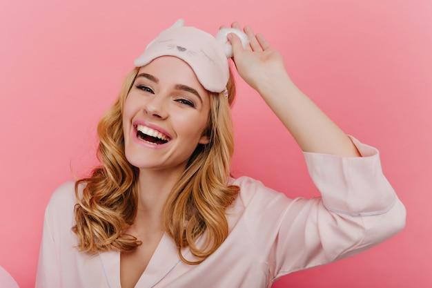 Nahaufnahmeaufnahme des spektakulären blonden mädchens, das im guten morgen lacht. positive kaukasische junge dame in der trendigen schlafmaske lokalisiert auf rosa wand.