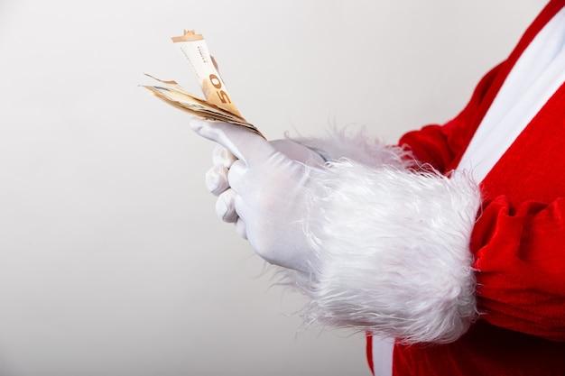 Nahaufnahmeaufnahme des weihnachtsmanns, der euro-rechnungen hält