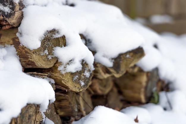 Nahaufnahmeaufnahme des weißen schnees, der oben auf trockenen wäldern sitzt, die aufeinander gestapelt werden