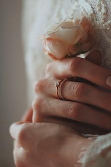 Nahaufnahmeaufnahme einer braut, die einen schönen diamantring trägt und eine rose hält