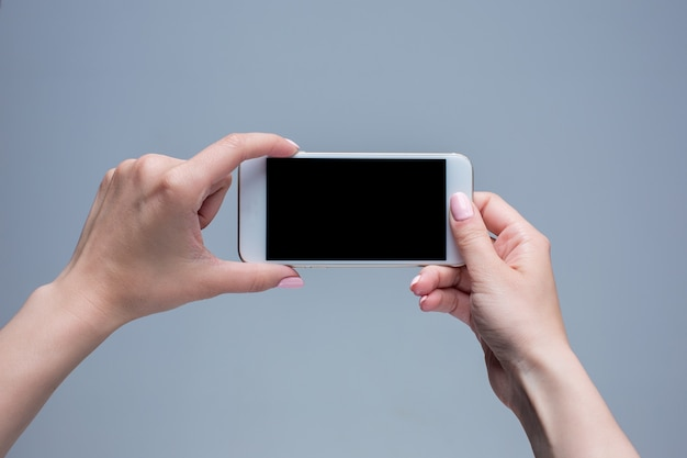 Nahaufnahmeaufnahme einer frau, die auf handy auf grauem hintergrund tippt. weibliche hände, die ein modernes smartphone halten und mit tiger zeigen. leerer bildschirm, um ihn auf ihre eigene webseite oder nachricht zu setzen.