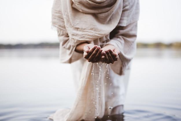 Nahaufnahmeaufnahme einer frau, die ein biblisches gewand trägt, das wasser mit ihren handflächen hält