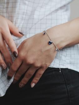 Nahaufnahmeaufnahme einer frau, die ein modisches silbernes bettelarmband trägt
