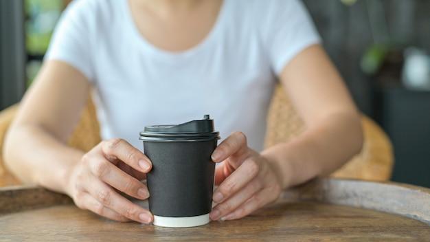 Nahaufnahmeaufnahme einer frau, die eine kaffeetasse zum mitnehmen auf dem tisch hält.
