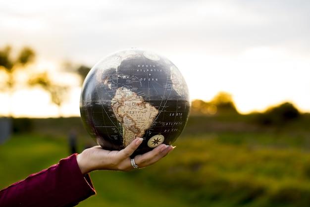 Nahaufnahmeaufnahme einer frau, die einen globus hält
