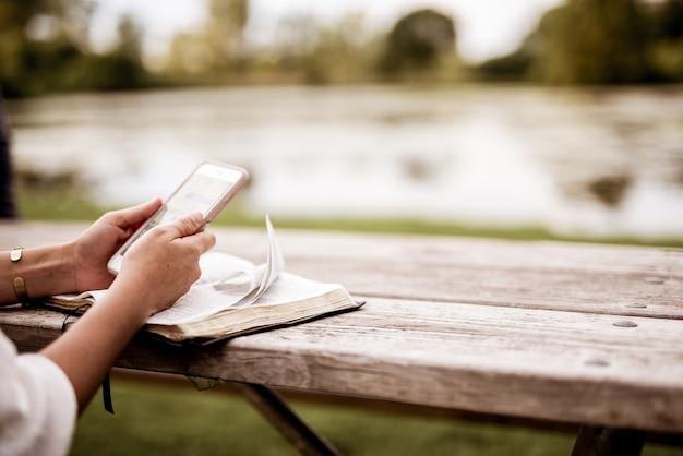 Nahaufnahmeaufnahme einer frau, die ihr smartphone mit der bibel benutzt