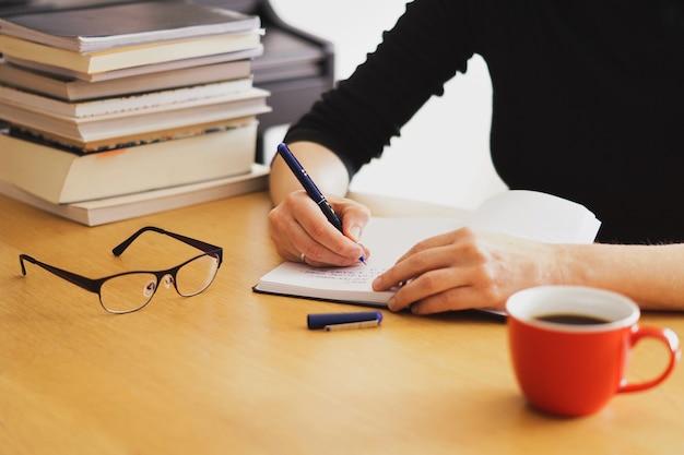 Nahaufnahmeaufnahme einer frau, die von zu hause aus mit einer roten kaffeetasse in der nähe arbeitet oder studiert