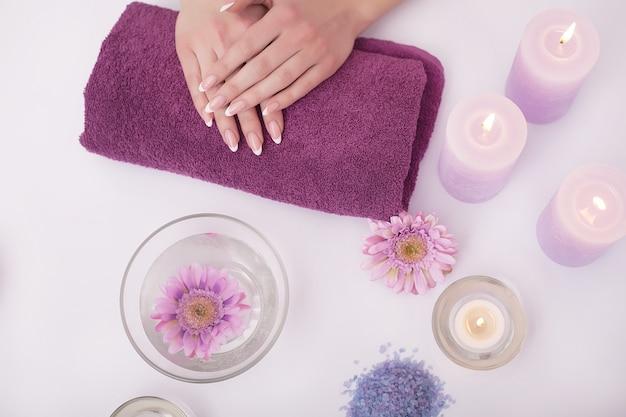 Nahaufnahmeaufnahme einer frau in einem nagelstudio, die eine maniküre durch eine kosmetikerin mit watte mit aceton erhält. frau, die nagelmaniküre erhält. kosmetikerin feilt nägel an einen kunden