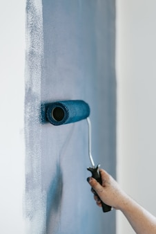 Nahaufnahmeaufnahme einer frau unter verwendung von farbrollern mit der farbe blau