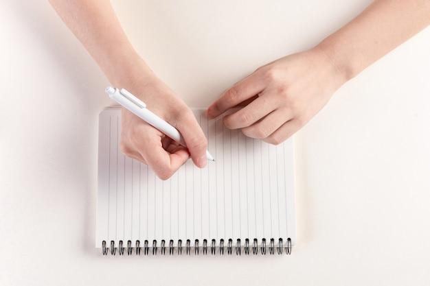 Nahaufnahmeaufnahme einer hand, die ein tagebuch ausfüllt
