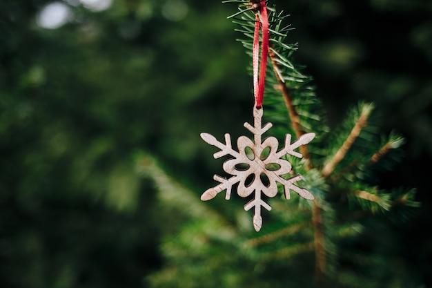 Nahaufnahmeaufnahme einer hölzernen flocke auf dem weihnachtsbaum