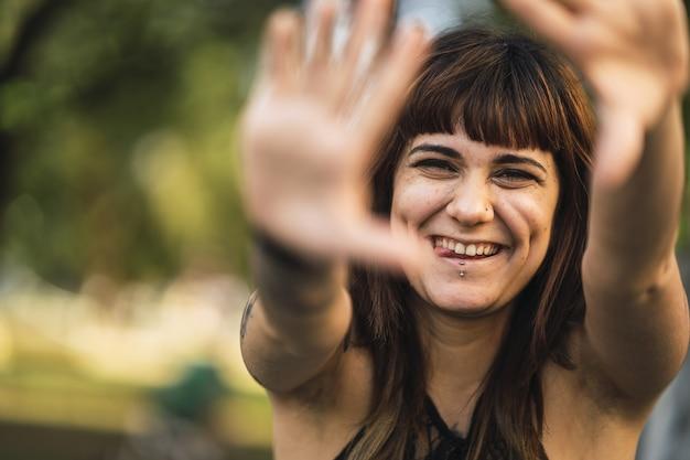 Nahaufnahmeaufnahme einer jungen attraktiven kaukasischen frau mit tätowierungen, die ein niedliches gesicht machen