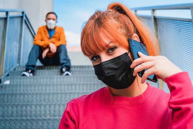 Nahaufnahmeaufnahme einer jungen frau, die am telefon spricht, und eines mannes, der auf treppen sitzt