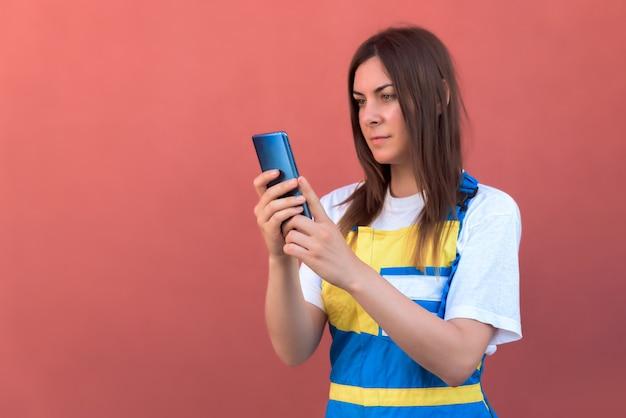 Nahaufnahmeaufnahme einer jungen frau mit ihrem smartphone posierend