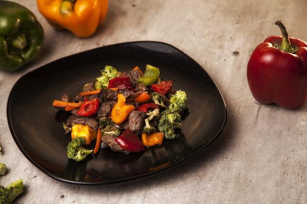 Nahaufnahmeaufnahme einer köstlichen und gesunden mahlzeit mit rindfleisch und gegrilltem gemüse in einem schwarzen teller
