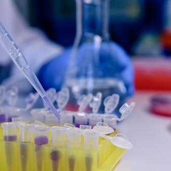 Nahaufnahmeaufnahme einer person, die einen coronavirus-test mit pipetten durchführt