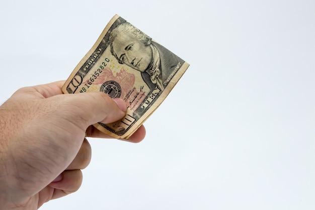 Nahaufnahmeaufnahme einer person, die einen dollarschein über einem weißen hintergrund hält