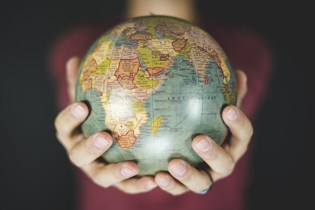 Nahaufnahmeaufnahme einer person, die einen kleinen globus mit zwei händen hält
