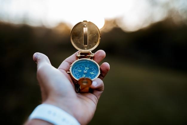 Nahaufnahmeaufnahme einer person, die einen kompass hält
