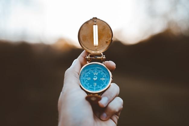 Nahaufnahmeaufnahme einer person, die einen kompass mit einem entgrateten hintergrund hält