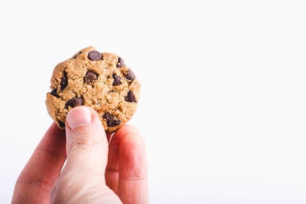 Nahaufnahmeaufnahme einer person, die einen schokoladenkeks hält lokalisiert auf weiß