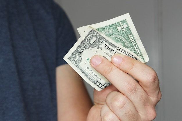 Nahaufnahmeaufnahme einer person, die einen us-dollar-schein auf seiner hand hält
