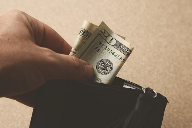 Nahaufnahmeaufnahme einer person, die etwas geld in seine lederbrieftasche steckt