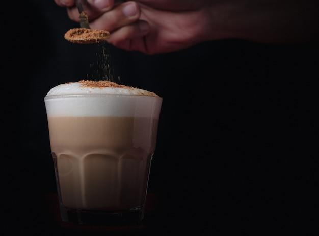 Nahaufnahmeaufnahme einer person, die kaffeepulver auf einen kaffee gießt